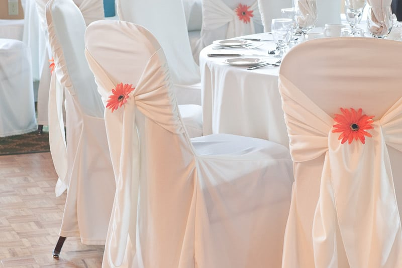 Portion of a wedding table with white linen, surrounded by chairs and white chair covers with an ornamental orange daisy on the back of each of them.